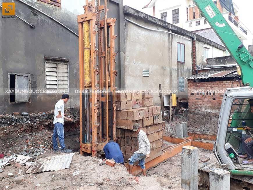 Công nhân thi công ép cọc bê tông gia cố móng ngôi nhà phố
