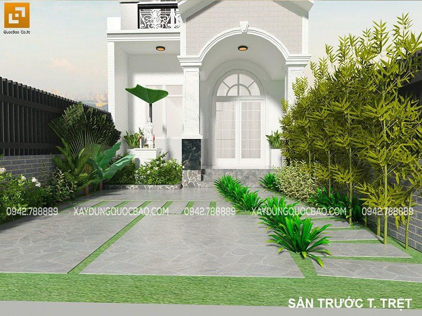 Khoảng sân trước nhà lát gạch chống trơn, trải thảm cỏ xanh tươi, có tượng Quán Thế Âm uy nghi