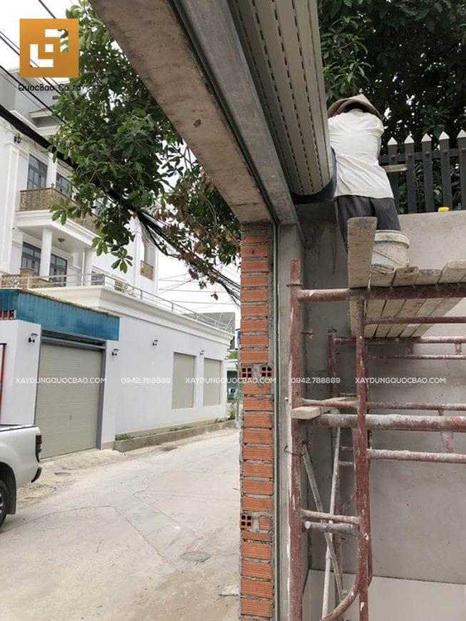 Công nhân đang lắp đặt cửa cuốn ở cổng nhà
