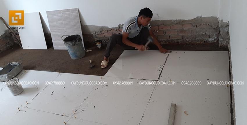 Công nhân thi công lót gạch nền phòng khách