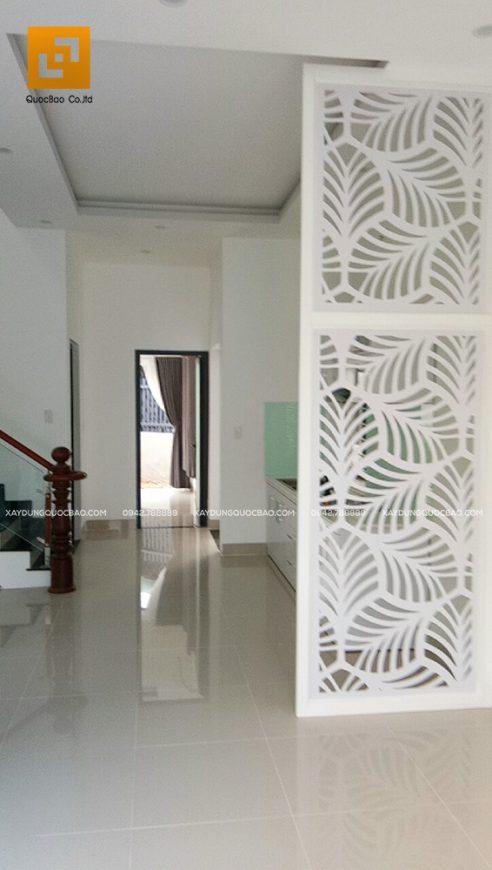 Vách ngăn hoa văn giữa phòng khách và phòng bếp mang lại nét duyên cho tầng trệt