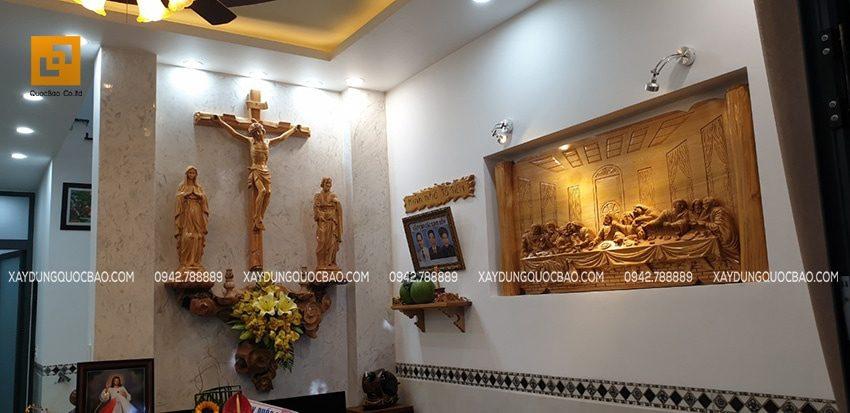 Phòng khách bài trí tranh tượng Thiên Chúa và bàn thờ tổ tiên