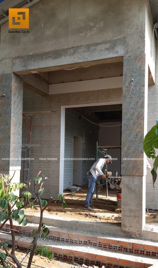 Phía ngoài Biệt thự, công nhân đang thi công ốp gạch, đá trang trí khu vực mặt tiền