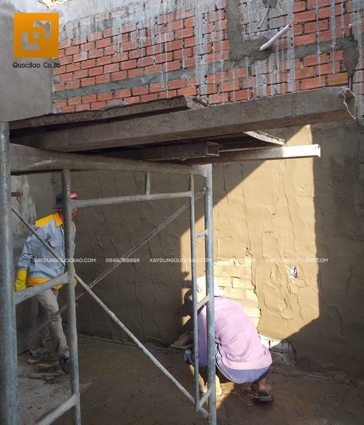 Công nhân tô trát xi măng các bức tường bên trong biệt thự
