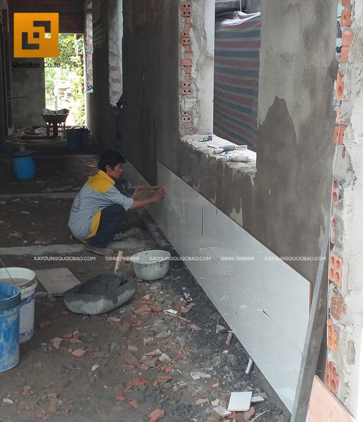 Bên trong biệt thự, đội thi công đang ốp gạch chân tường