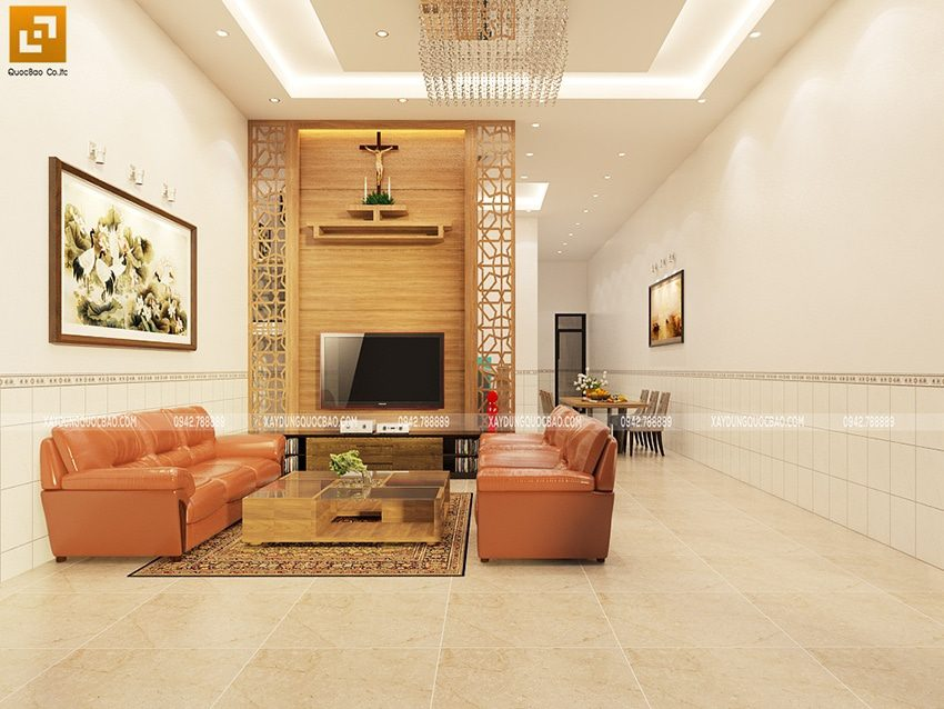 Thiết kế nội thất phòng khách sang trọng với bộ bàn ghế sofa, tranh treo tường, kệ tivi và tượng thờ Chúa trang nghiêm
