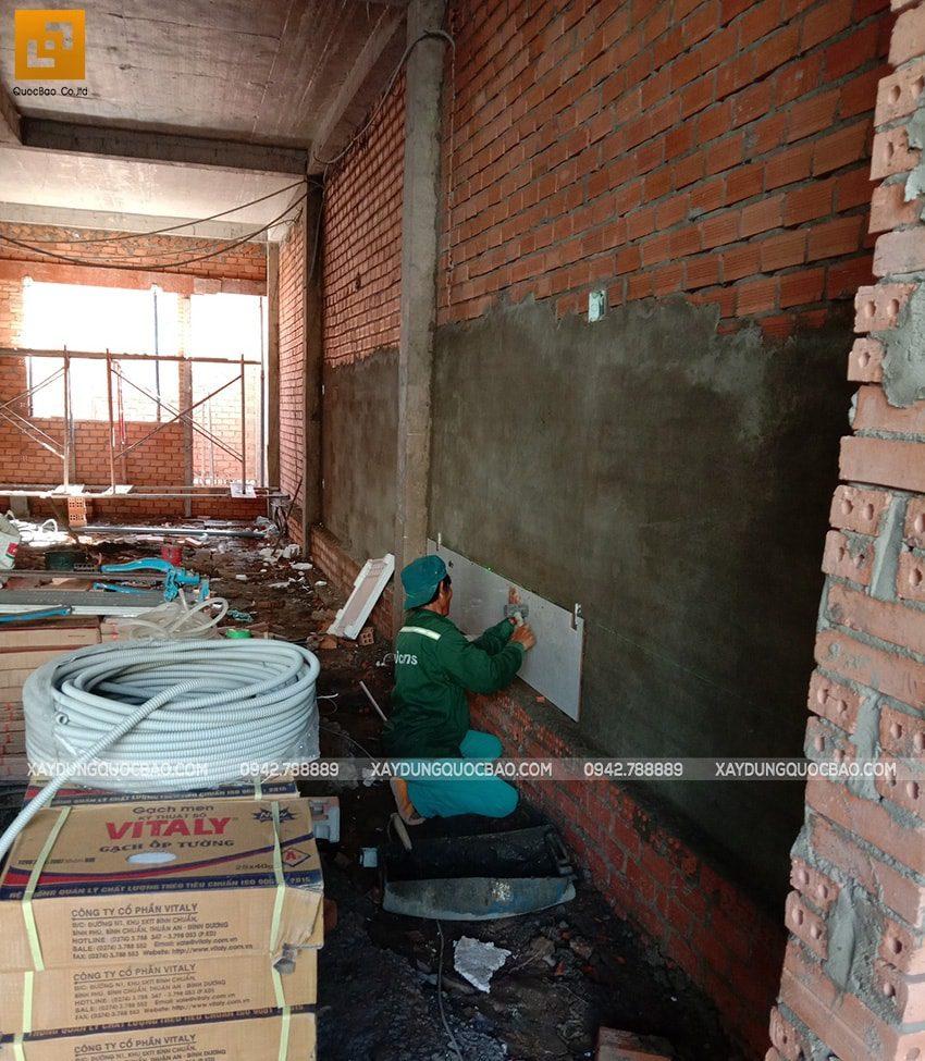 Công nhân đang ốp gạch trang trí tường nhà