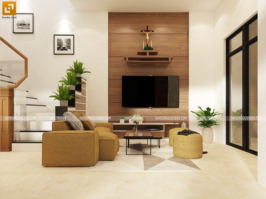 Phòng khách được trang trí nhiều chậu cây xanh, tivi treo cứng cáp trên vách gỗ sang trọng