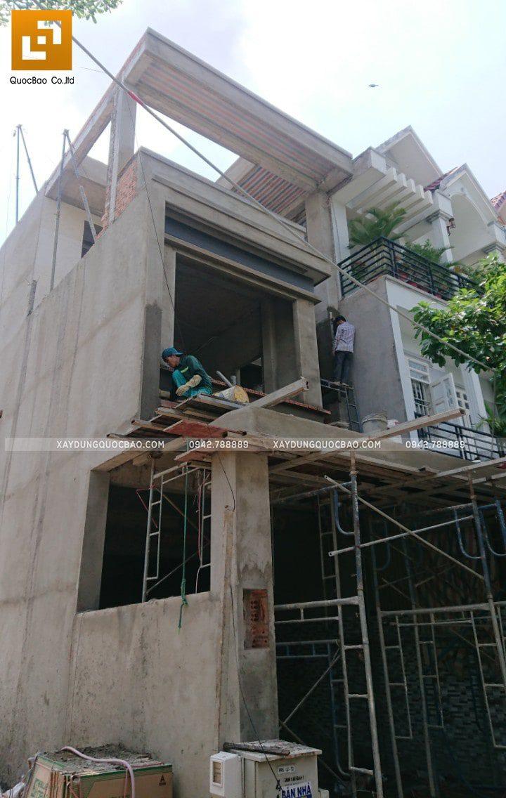 Công nhân thi công ốp dán gạch trang trí khu vực mặt tiền nhà