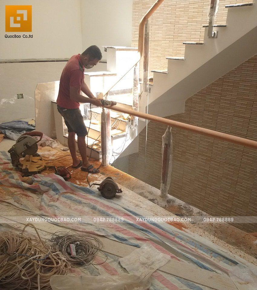 Bên trong nhà, đội thi công lan can cầu thang đang gia công chi tiết tay vịn bằng gỗ
