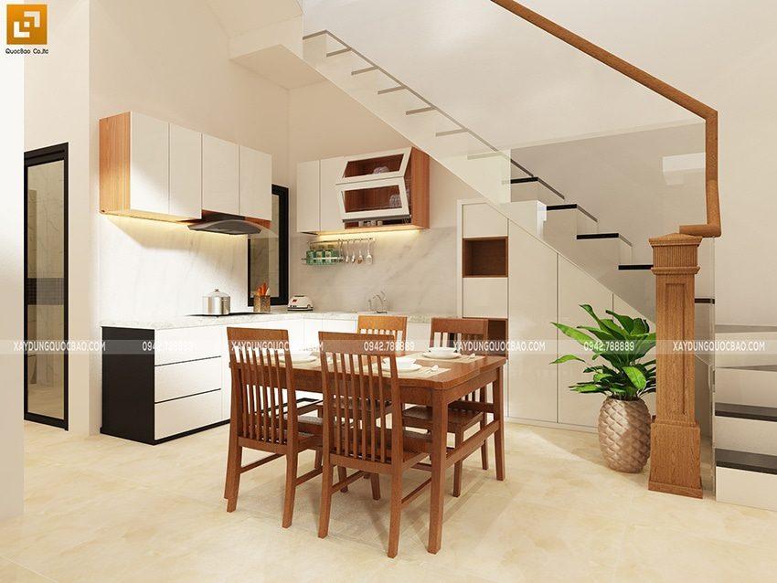 Phía sau phòng khách là khu vực phòng bếp được bố trí bàn ăn, kế bên là cầu thang dẫn lên lầu 1. Không gian phòng ăn rất thông thoáng, gần khu vực bếp tiện lợi cho gia đình khi thưởng thức bữa cơm mỗi ngày.