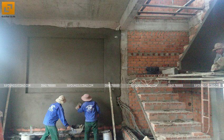 Các công đoạn luân phiên được tiến hành cả trong và ngoài nhà. Đội thi công đang tô trát các bức tường bên trong nhà