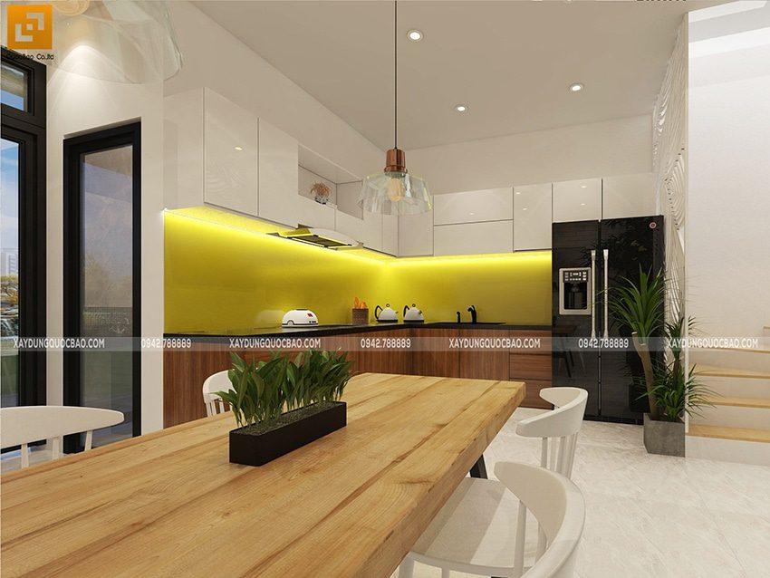 Giữa phòng bếp bày biện 1 bàn ăn lớn, khu vực bếp được trang bị đầy đủ đồ gia dụng thiết yếu cho người nội trợ