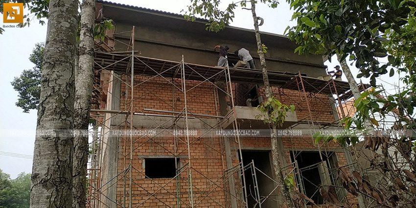 Công nhân thi công tô trát xi măng tường bên ngoài nhà