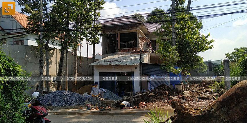 Phía trước nhà, công nhân đang thi công trụ, cột của cổng nhà