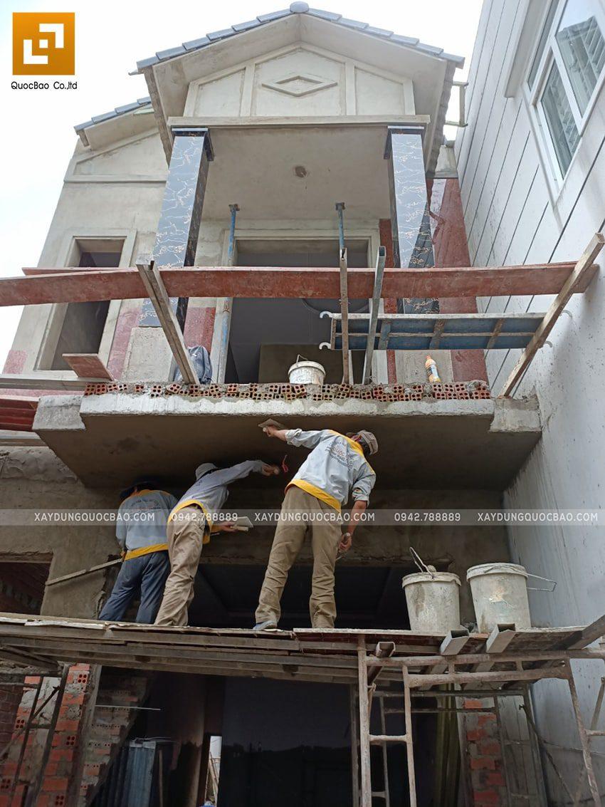 Công nhân thi công tô trát mặt tiền ngôi nhà mái thái