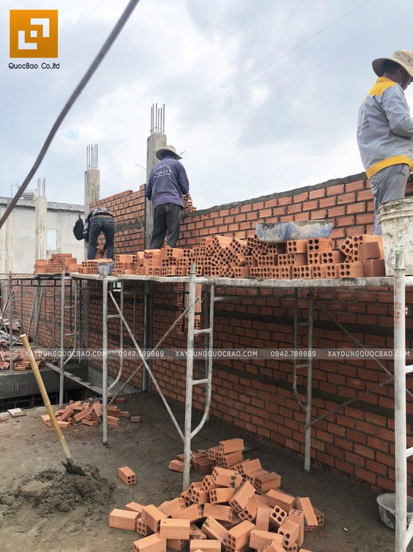 Công nhân thi công xây tường bao của ngôi nhà - Ảnh 1