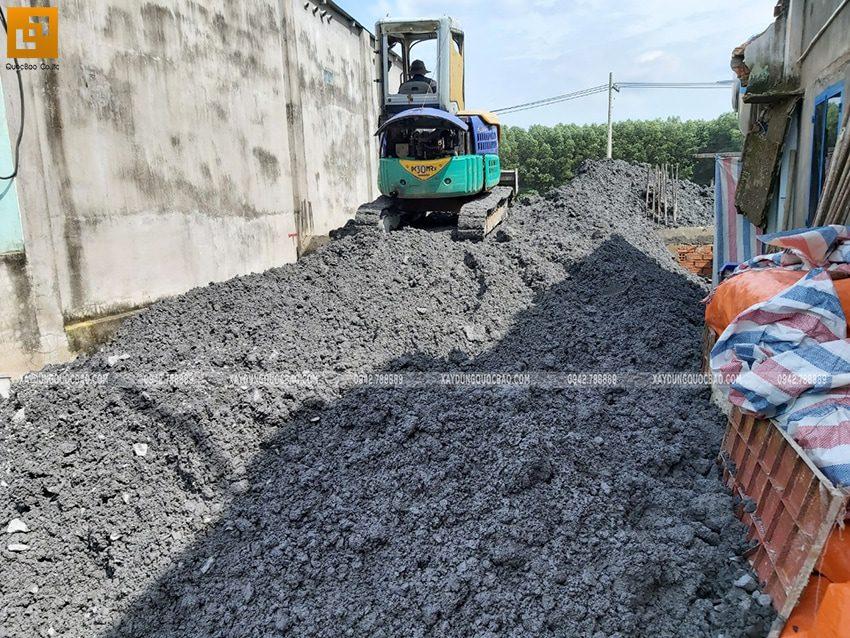 Công nhân vận hành xe múc, xe ủi đổ đất móng nhà