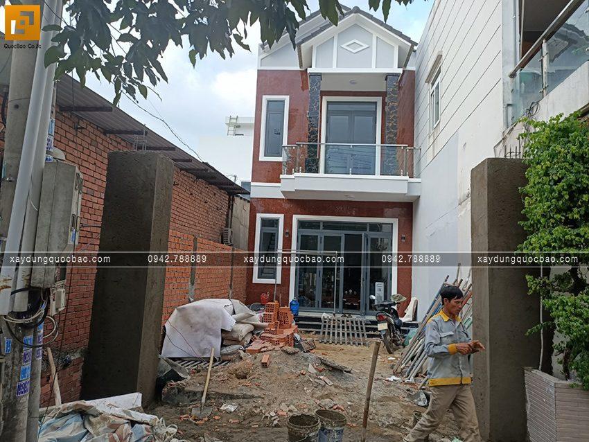 Phía ngoài nhà, đội thi công đang hoàn thiện phần tường và cổng