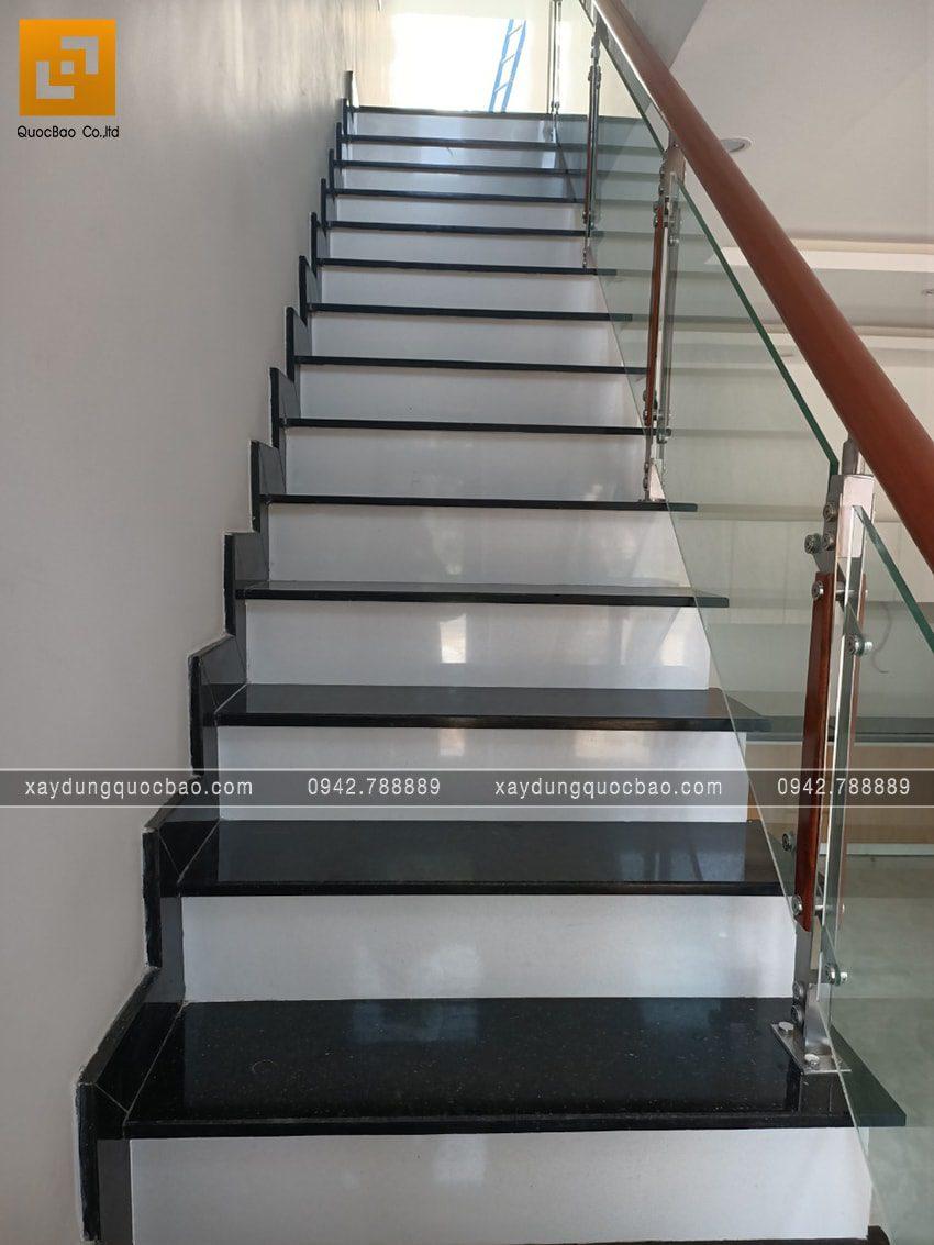 Cầu thang ốp đá hoa cương Granite, tay cầm bằng gỗ, vách kính bảo vệ sang trọng