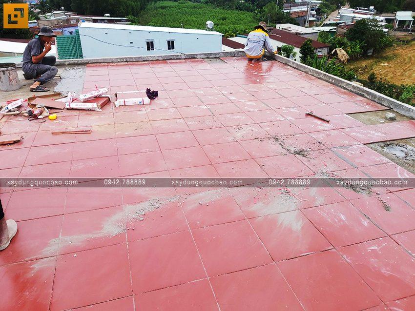Công nhân đang lát gạch ngoài trời ở khu vực sân thượng